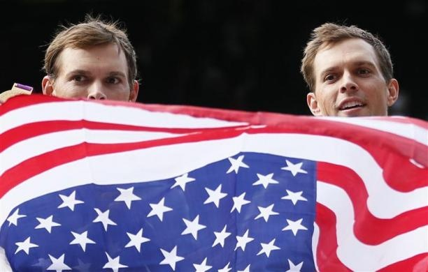 Brothers Bob Bryan (R) and Mike Bryan of the U.S. hold their country's flag as they stand with their gold medals during the presentation ceremony after they defeated France's Jo-Wilfried Tsonga and Michael Llodra in the men's doubles tennis final match at the All England Lawn Tennis Club during the London 2012 Olympic Games August 4, 2012.  REUTERS/Stefan Wermuth - http://www.PaulFDavis.com/success-speaker (info@PaulFDavis.com)