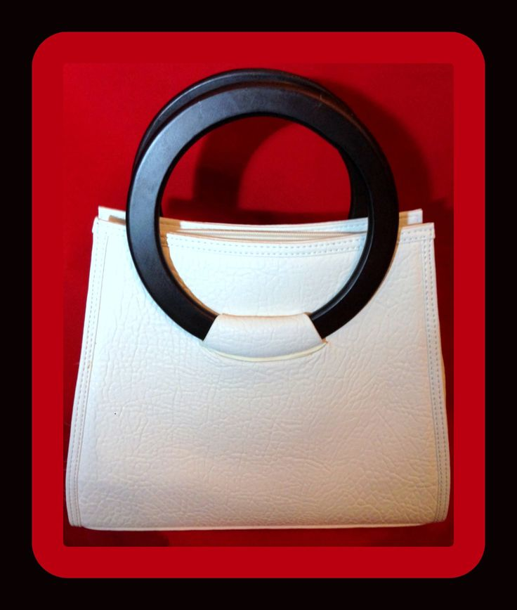 """White pebbled leather handbag with round, brown faux wooden handles. PU. ~ Zip top closure ~ Wood handles; 3.5"""" drop ~ Detachable shoulder strap included; 17"""" ~ Interior includes: three open pockets a"""