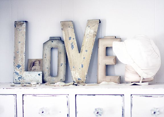 Love - letters in different sizes - maybe gold glitter placed in the square opening of back wall - feature while looking from bar