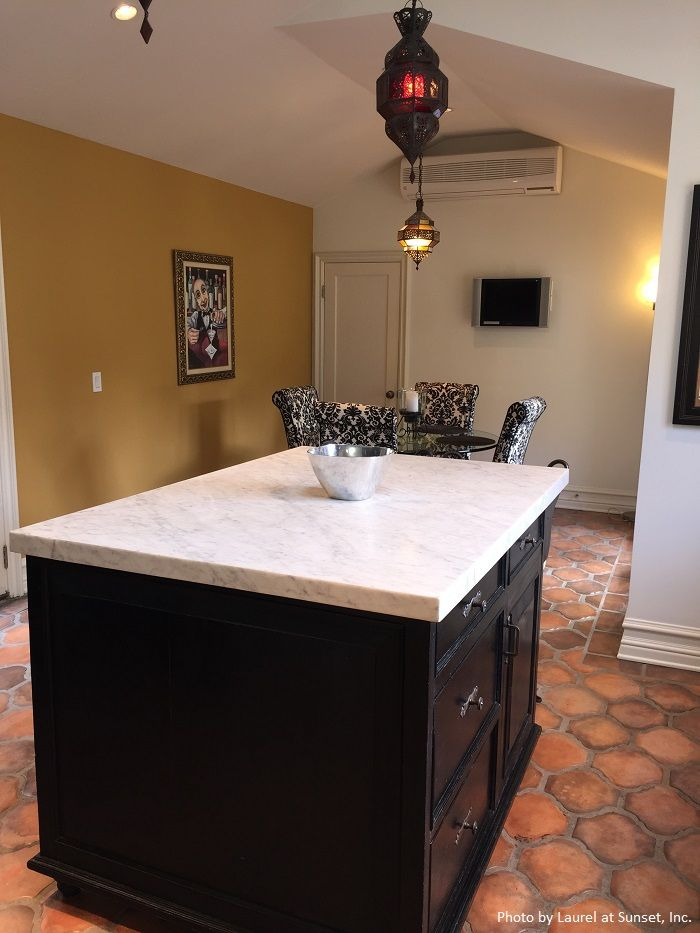 White baseboards, marble countertop, damascus dining room chairs and Mediterranean tile flooring gives this kitchen a ton of personality. Click on the image to find out how much a kitchen remodel cost in your area.