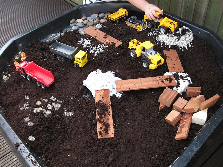 """Construction small world play - various vehicles including diggers & trucks, large rocks, pieces of wood, fish tank gravel, pebbles, decorative stones & soil (as didn't have enough sand for the base) ("""",)"""