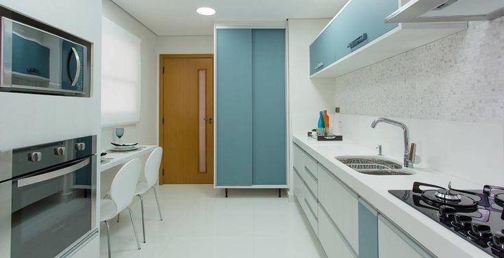 Cozinha prática e funcional tem pastilhas de cerâmica e móveis brancos com detalhes em azul petróleo. Projeto da arquiteta Daniela Inês.