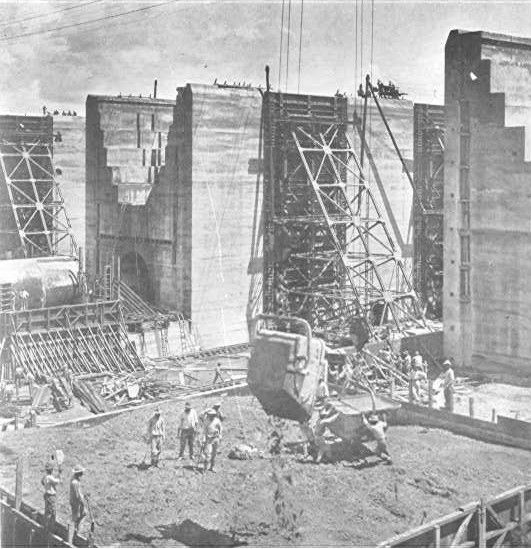 Receiving the Concrete (Note the men standing on top of the wall on the extreme left.  The largest amount of concrete laid in any one month at Gatun is 89,401 cubic yards.  The average cost of the concrete per yard in place for 1910 was $7,355, including plant charges and division expenses.  To build the Gatun locks 2,250,000 barrels of cement will be required.)
