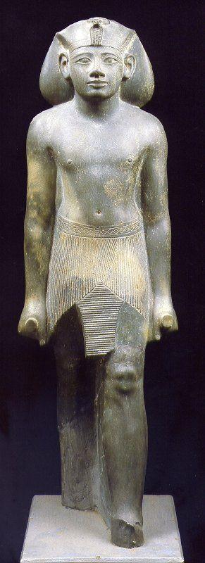 """Son muchas las estatuas y figuritas que se realizaron durante los 25 años de reinado de Amenhetep II. Este faraón fue célebre por su fuerza física y ese aspecto se refleja en sus estatuas. Los escultores subrayan la musculatura de sus brazos, así como el pecho amplio y bien desarrollado. Se le representa con rostro juvenil, y en la boca presenta la llamada """"sonrisa tutmósida""""."""