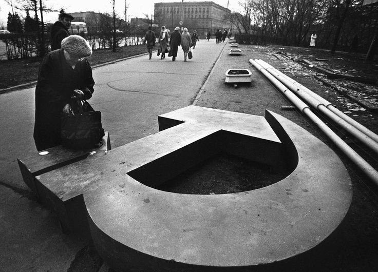 A woman reaches into her bag, which rests on a fallen Soviet hammer-and-sickle on a Moscow street in 1991. by Alexander Nemenov
