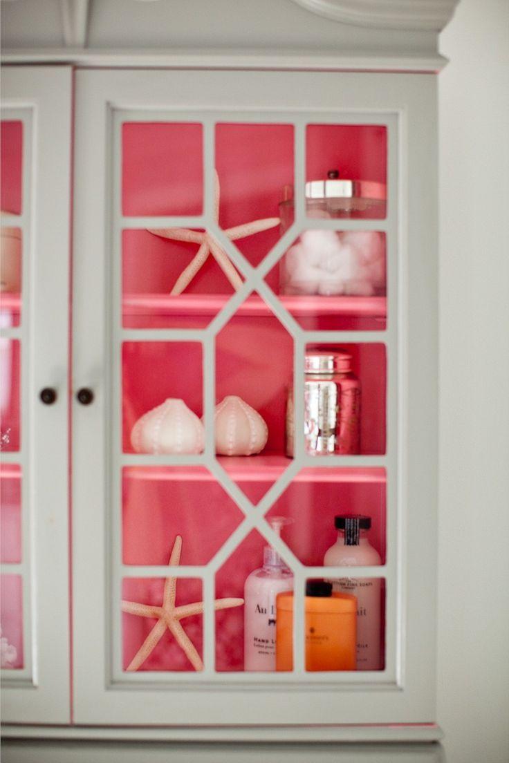 Pink shelves inside a white fretwork cabinet