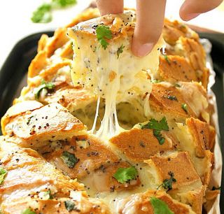 Loaded stuffed bread. Pour the butter-onion garlic mixture carefully into those X cracks using a small spoon and over the top of the bread. Fill those delicious cracks with the grated cheese.