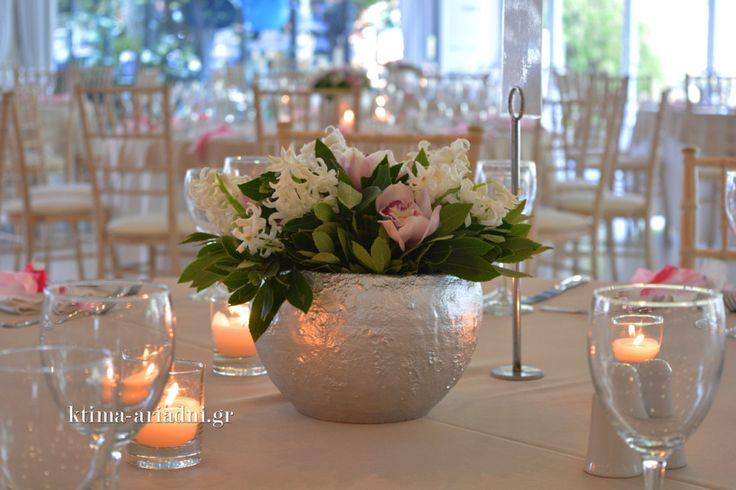 Κεντρική διακόσμηση με φρέσκα λουλούδια και κεριά σε χαμηλά γυάλινα κηροπήγια