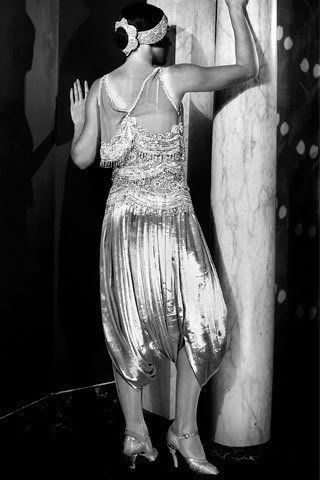 1920 - Conjunto Zouave  de Paul Poiret - O exótico conjunto Zouave combina com um top delicado com bordados e franjas com calças largas ao estilo do norte da África. O exostismo luxuoso de Poiret não vendeu bem na década de 1920 e a Maison fechou em 1929. (Cally Blackman - 100 Years of Fashion)