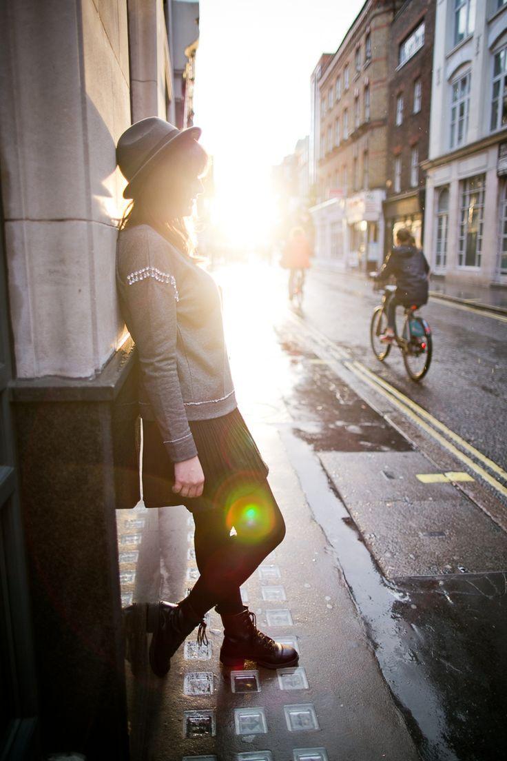 Look em tons neutros com moletom cinza com pedrarias no ombro saia preta meia calça coturno e chapéu
