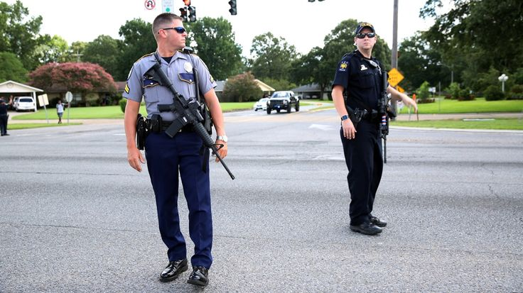Two suspects at large and one killed after gunfight near police headquarters in state's second largest city.