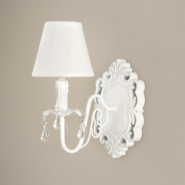A elegant french style wall light with a wooden carved plaque a fine linen shade and acrylic crystal effect droplets mounted on leaves around the iron arm