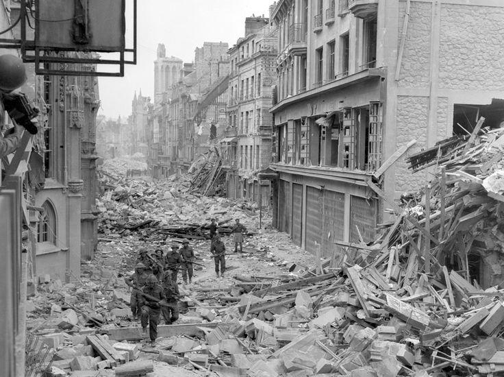 Des soldats canadiens patrouillent dans la rue Saint-Pierre après que les troupes allemandes ont été délogées de Caen en juillet 1944.