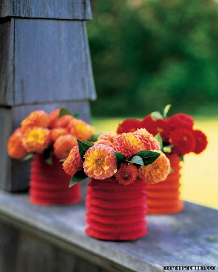"""Make a vase to match your flowers with a Chinese paper lantern and a small drinking glass. You'll find the accordion-style lanterns in many colors at party-supply stores. Trace the top of the glass onto the top of the lantern. Cut out that circle using scissors. Then slide in the glass, allowing the top of the lantern to catch on the lip of the glass, keeping the lantern """"open."""" Pour water into the glass, then add a handful of flowers, such as these zinnias, with their stems cut short..."""