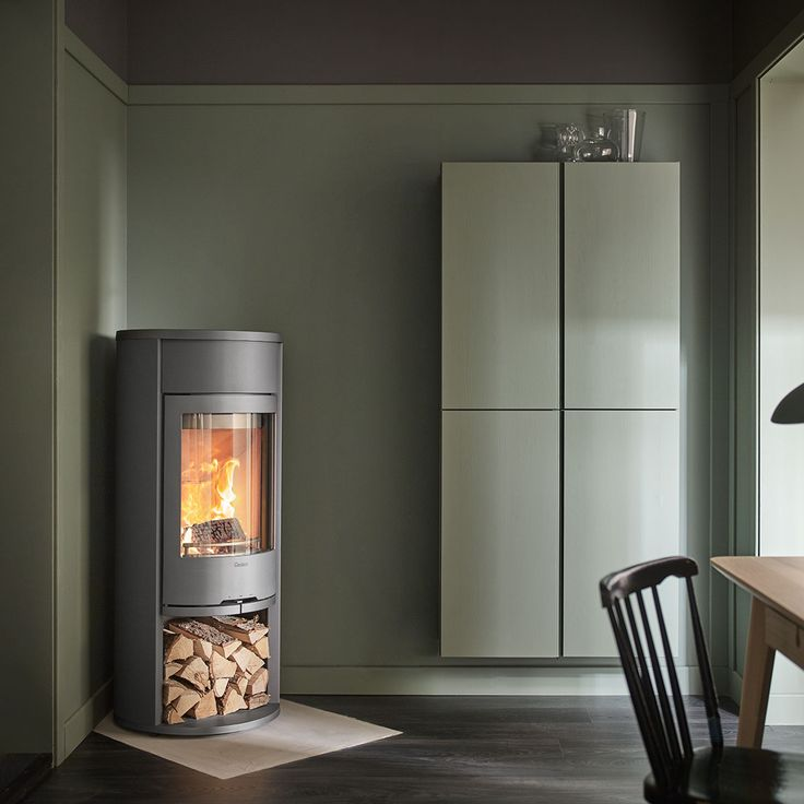 Contura 610 Style in grey with cast iron door. Choose between painted aluminium, soapstone or glass top,#woodburningstove #contemporarystove #woodenchair #greenwall #contura600 #conturastyle