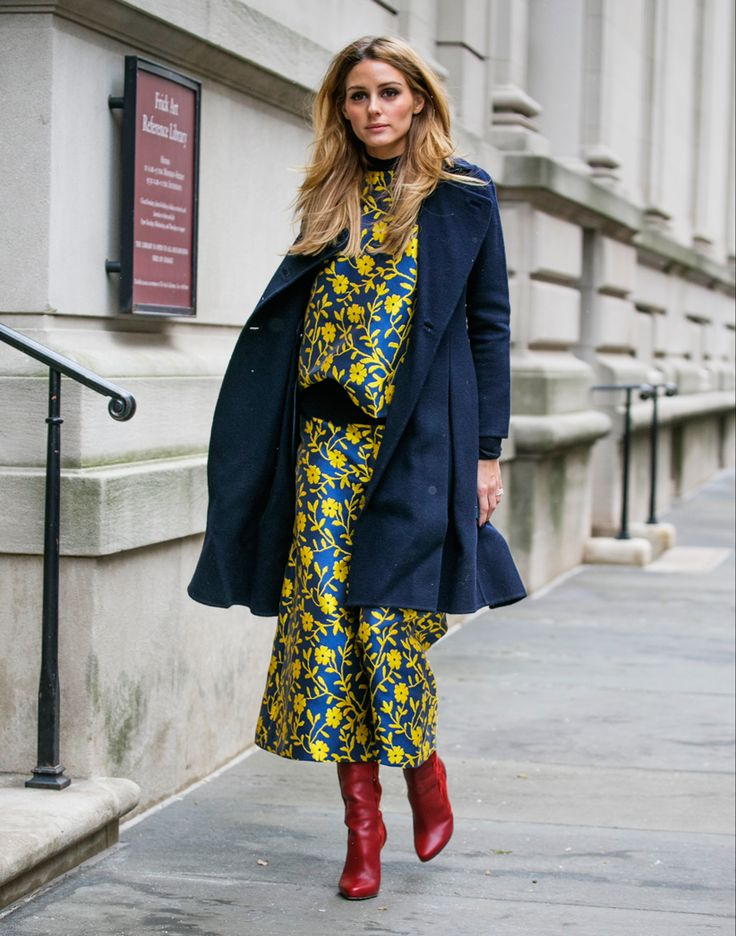 Red suede Christian Louboutin knee-high boots add a pop of color to this glam Carolina Herrera ensemble.