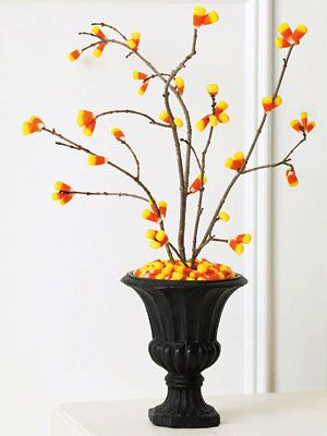 candy corn tree ~ pick a few clean-looking branches from your yard and hot-glue kernels onto them in clumps of twos and threes in various spots, concentrating on the ends and the Vs where the twigs branch off. Wedge the trunk of the branch into a small Styrofoam or floral square and rest it in the base of a vase. Fill the vase to the brim with corn to cover the Styrofoam