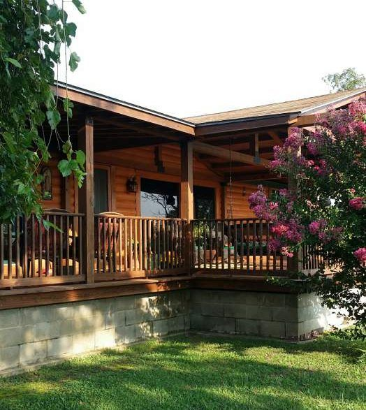 This complete double wide remodel in Arkansas is gorgeous with log siding, huge front porch, and a fully customized interior.