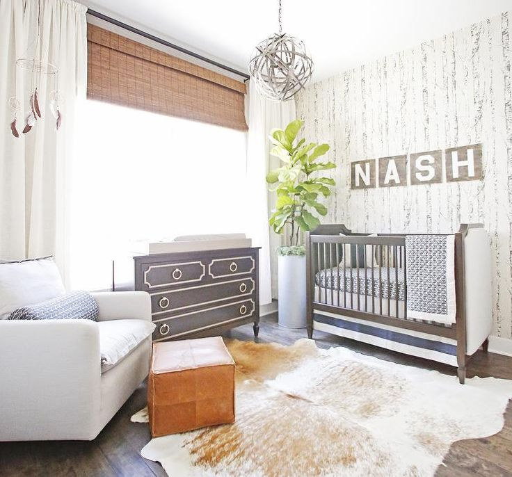 Rustic boy's nursery features an accent wall clad in Cole & Son Woods Wallpaper lined with a brown crib with white upholstered side panels, Newport Cottages Marcel Crib, dressed in Oilo Diamond Crib Sheet - Stone next to a fiddle leaf fig plant.