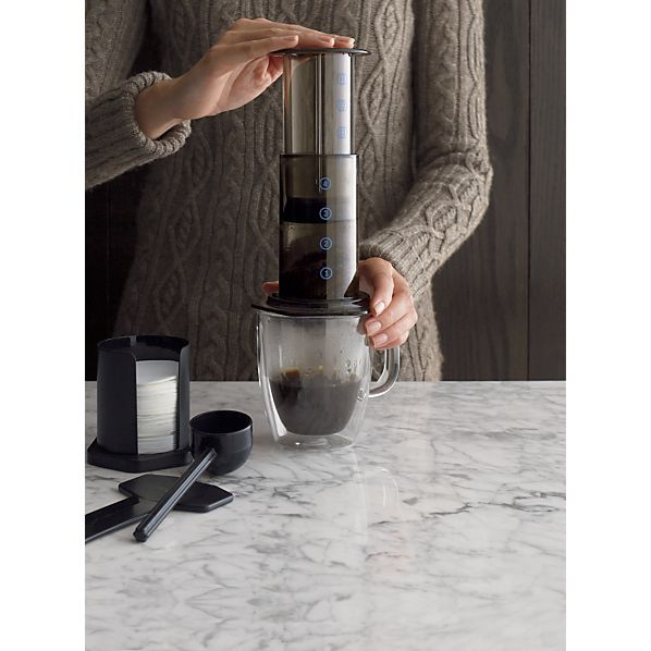 The Aerobie Aeropress coffee maker is a portable, plunger-style coffee press that produces coffee for espresso in less than one minute for drinking or mixing in lattes, cappuccinos and iced drinks. Immersion brewing system creates uniform extraction for full-flavored results. Unique micro-filters assure smooth, grit-free coffee. The Aeropress coffee and espresso maker includes a plunger press, scoop, funnel, tamper and filter holder. Lightweight press also brews tea.