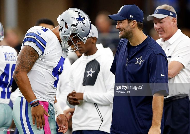 Dak Prescott #4, quarterback of the Dallas Cowboys talks with injured quarterback Tony Romo #8 prior to the game against the Cincinnati Bengals at AT&T Stadium on October 9, 2016 in Arlington, Texas.