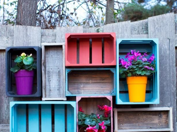"""Add open storage to your yard or garden with wooden crates grouped and installed along a fence or exterior wall. You will need: a variety of rustic wooden crates in an odd number /  1 1/2"""" exterior wood screws (for metal or brick surface installations,  metal or masonry screws may be required) / drill / camera / potted  plants / exterior paint or sealer / paint brush"""