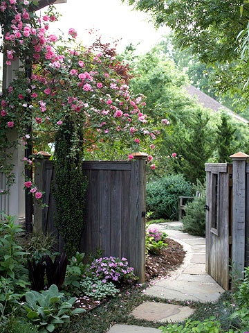 Side Yard - Paths get us to and from where we're going so why not put something beautiful to look at along the way? This climbing rose at the gate reblooms so is almost always covered with beautiful pink blooms. The gray patina of the wood gate and the green of the plantings and their various textures paint a lovely picture.  #bhg.com