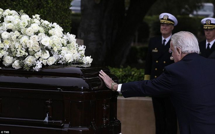 Former Canadian prime minister Brian Mulroney pauses at Nancy Reagan's casket at her grave...