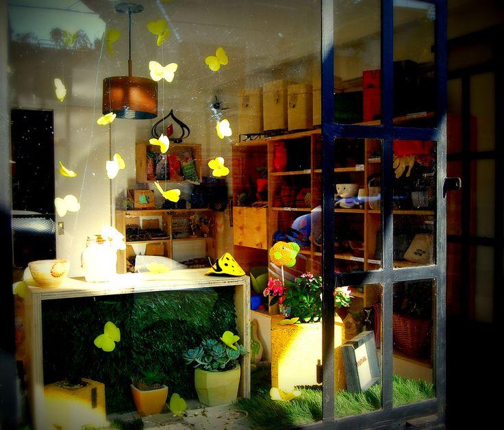 Vidriera con mariposas amarillas de La Posta Eco, vista desde afuera