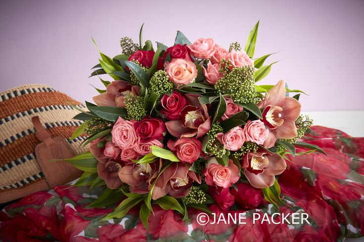 A rich and fruity design mixing coral and two toned apricot Roses with blush Spray Roses, striking Cymbidium Orchids, and a stunning combination of tropical verdure.