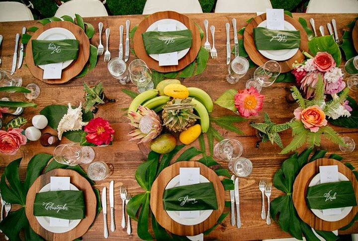Charger plates placed on tropical leaves and leaf place cards