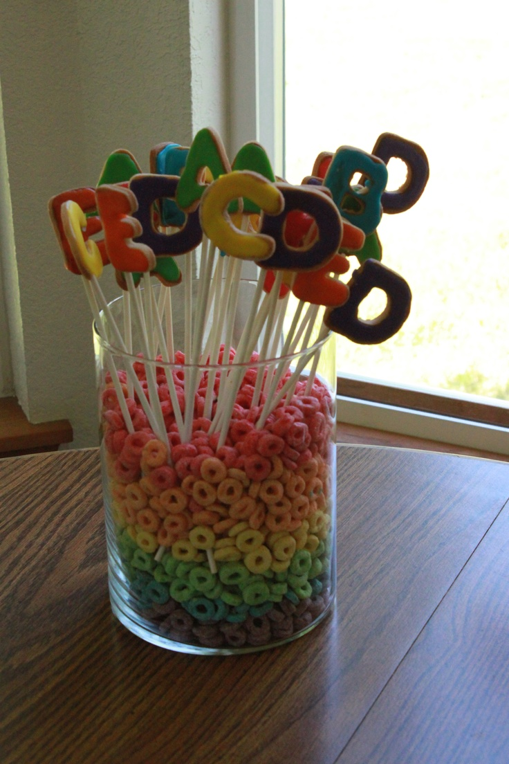 Homemade alphabet cookies on sticks displayed in a vase full of Fruit Loops. And yes, I separated all of the colors. #cookies #alphabet #party #birthday #decorations