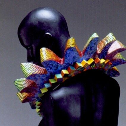 In the jewellery world Marjorie Schick is a complete original. Over forty years she has built up an impressive oeuvre. Her colourful wood or papier-maché constructions make a powerful visual statement when worn as wearable objects. Book: Sculpture to Wear. The Jewelry of Marjorie Schick.