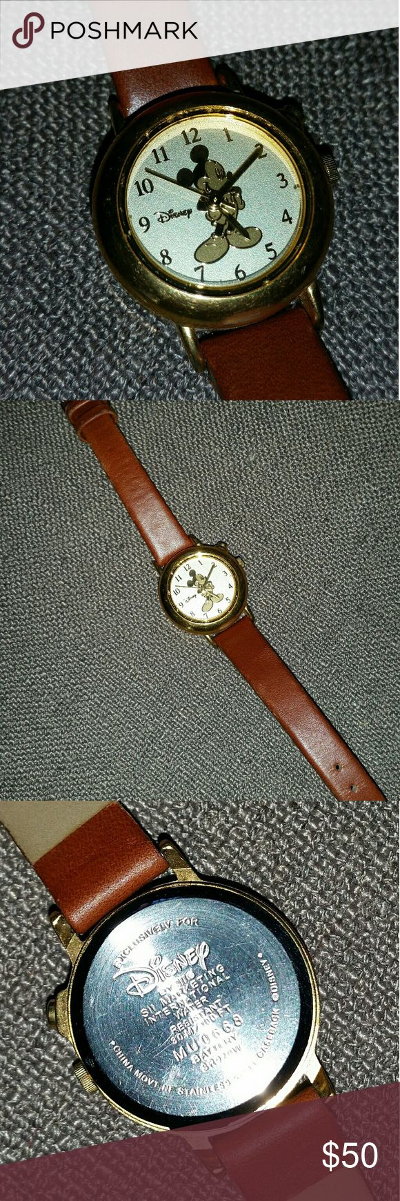 Authentic Disney Mickey Mouse Watch Adorable, yet dressy, woman's gold-tone Mickey Mouse Watch with brown leather band. Like new, it's distinctly Disney! It does need a new battery. I believe it plays the Mickey Mouse theme song when the top button is pressed. Disney Accessories Watches