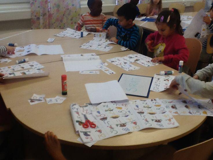 Eleverna letar efter sina bokstäver och limmar ihop sina namn.