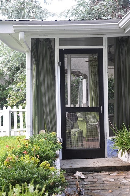floor to ceiling green curtains in a screened off porch ...