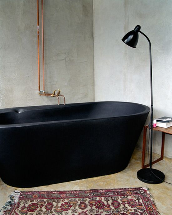 sleek black tub and exposed copper pipes