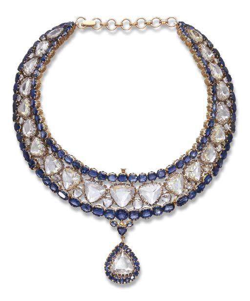 AN IMPRESSIVE INDIAN DIAMOND AND SAPPHIRE NECKLACE   The articulated openwork collar, composed of a series of triangular-shaped table-cut diamonds, enhanced by similarly-shaped diamond spacers, to the oval-cut sapphire trim, suspending a pendant of similar design, 14½ ins.