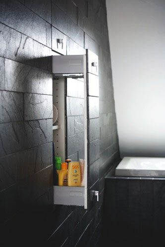 Concealed bathroom storage. The wallcover is continuous across drawer faces, with only the handles visibly obvious; coordinate those with the fixtures.