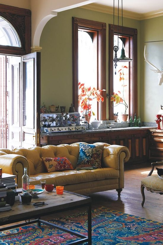 Yellow button-tufted chesterfield, pea green walls, wood tones with eclectic (trad + industrial + period) furniture pieces