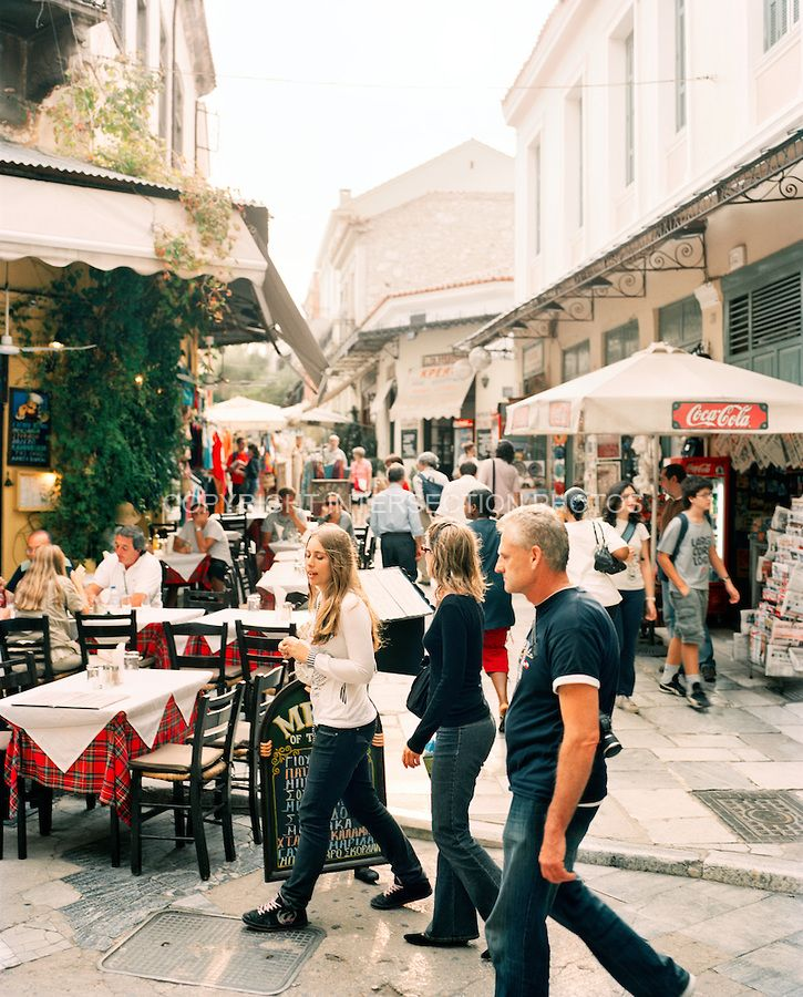 People walk in and around cafes and restaurants in an area called Thissio - Athens, Greece