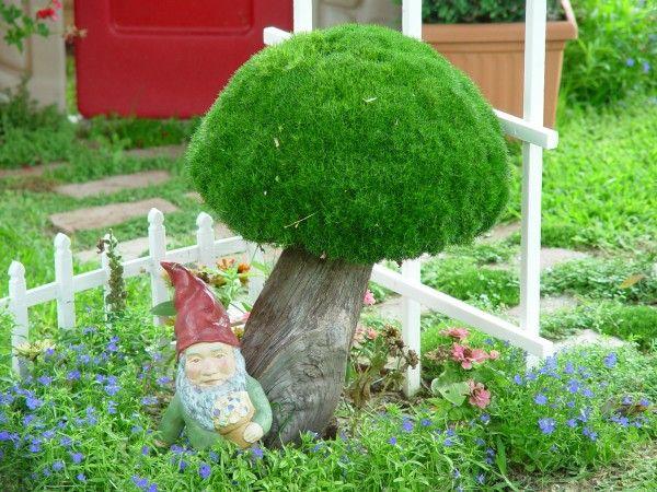 Mushrooms in the garden; inverted moss basket set on a wooden log.