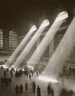 Straight from the NYC Dept. of Records description -   Shafts of sunlight penetrating through   upper windows down into Terminal concourse, crowds gathering near information kiosk