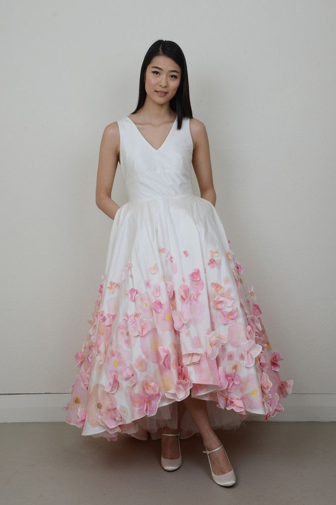 'In a Bed of Flowers' is a modern and show stopping bridal dress! The silk dupion bodice features a flattering v-neck cut with a wide contoured waistband. The skirt is shorter in the front and features a train at the back and has been hand painted and also appliqued with painted flowers sewn on top.