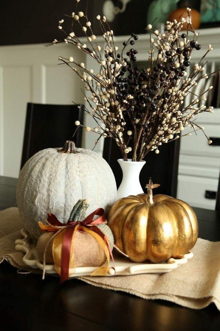 déco de table automnale réalisée en citrouilles décorées de peinture or/blanche et un bouquet de baies peintes en noir et blanc