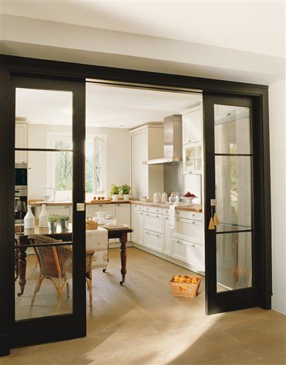 Glass pocket doors lead to kitchen for functional and aesthetic framing