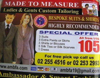 In Thailand zie je veel kleermakers die staande voor de deur van hun zaak klanten naar binnen trachten te manoeuvreren.