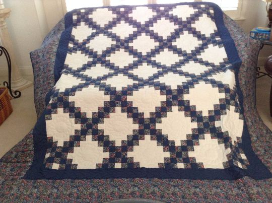 "This beautiful quilt will fit a queen size bed nicely. The size is 99"" x 112"". The patchwork is created in fabric of blue print, solid blue and white. There is a solid border surrounding the Irish cha"
