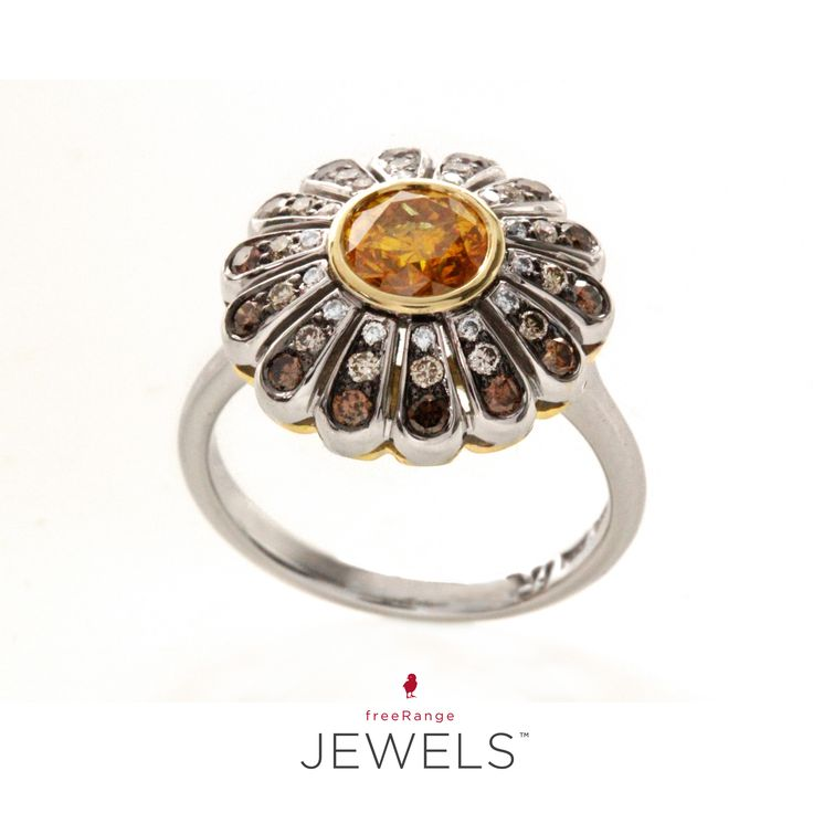 Think of looking into a rock pool on a beautiful clear day, with the sun twinkling off the water, and deep down is the gentle movement of an urchin, catching the sun's ray's in a splendour of colour. Now picture all of that on your finger.  The centre stone, a Fancy Yellow Diamond with 14 petals of white, cognac and tinted diamonds.  Spectacular, isn't it?