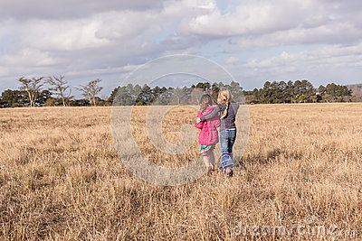 Young girls walking holding comforting scared friend back to parents at camp in wilderness reserve in countryside